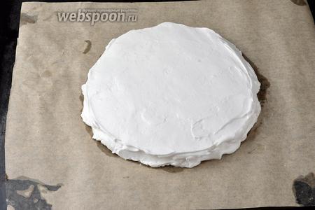 Выложить на противень пергаментную бумагу. Нарисовать круг, диаметром такой же, как испечённый бисквит. Смазать круг подсолнечным маслом (1 ст. л.). Выложить в круг взбитые белки, разровнять.