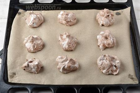 Порциями выложить массу на противень с пергаментной бумагой. Не забудьте оставить между порциями теста достаточно места, так как безе во время выпечки сильно подрастает.