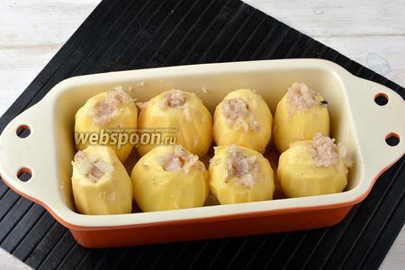 Форму для запекания, с высокими бортиками, смазать небольшим количеством сливочного масла (1 ст. л.). В форму, отверстиями вверх, выложить картофель. Нафаршировать картофель подготовленным фаршем.