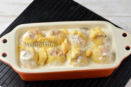 Соединить сливки с водой и солью (0,5 ч. л.). Залить сливочную смесь между картофелем. Сверху разложить кусочки сливочного масла.