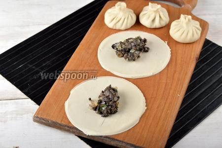 Раскатать тесто толщиной 2 мм, вырезать кружки диаметром 10-12 сантиметров. На середину кружков выложить 1 полную столовую ложку начинки. Сформировать хинкали.
