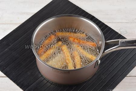 В толстостенной кастрюле хорошо разогреть подсолнечное рафинированное масло (200 мл). Порциями опускать в масло сформированные палочки и обжаривать до золотистого цвета.