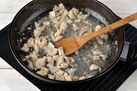 Окорочок (400 г) вымыть и обсушить. Срезать из окорочка мясо, порезать небольшими кусочками и обжарить на подсолнечном масле (3 ст. л.) 3-4 минуты.