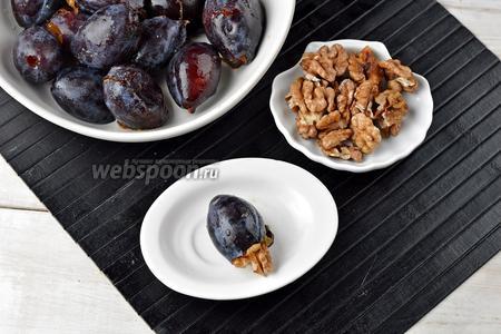 Нафаршировать каждую сливу половинкой грецкого ореха.