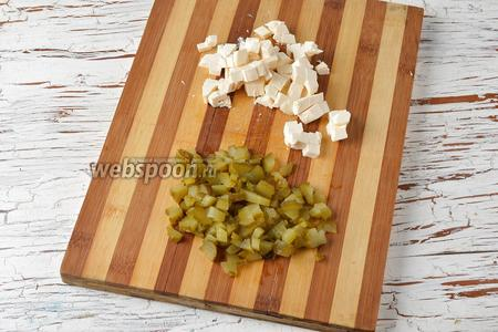 Солёные огурцы (80 г) и плавленый сыр (100 г) нарезать небольшими кубиками.