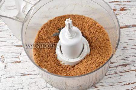 Овсяное печенье (200 г) поломать, поместить в чашу кухонного комбайна (насадка металлический нож). Измельчить до образования мелкой крошки.