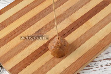 Набрать полную столовую ложку, с верхом, массы и скатать из неё конус. В центр вставить шпажку.