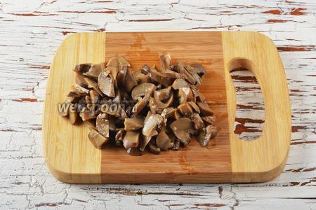 Шампиньоны (100 г) вынуть из маринада и нарезать небольшими кусочками.