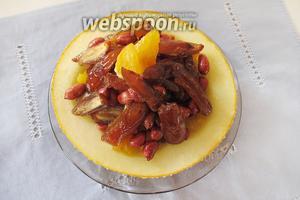 Выкладываем финики и арахис на дыню и украшаем дольками апельсина.