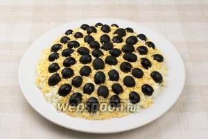 На желтки выложить половинки маслин.