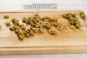 Оливки порезать на половинки.