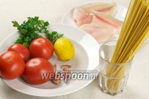 Для приготовления спагетти с рыбой возьмём: спагетти из твёрдых сортов пшеницы, филе тилапии, помидоры, чеснок, сливочное масло, зелень и лимон.