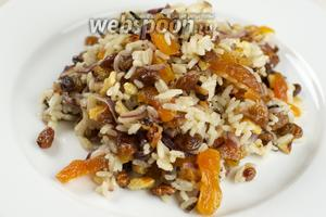 Выложить обжаренный лук с курагой, добавить рис, орехи и изюм, который предварительно надо отжать. Всё заправить оливковым маслом и посолить по вкусу.