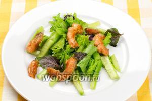 Выложить в тарелку огурцы с листьями салата, а сверху кусочки обжаренной сёмги — подавать сразу.