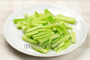 Огурцы помыть, очистить от кожуры и порезать брусочками длинной 4-5 см.