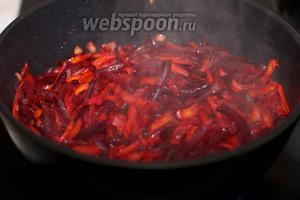 Разогреть на сковороде растительное масло и обжарить в нём лук 5 минут, а затем добавить морковку и свёклу - всё тушить 25 минут под крышкой.