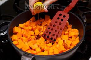 Добавить в сковороду тыкву, 80 г сахара, выдавить половину лимона, всё тщательно перемешать, накрыть крышкой и тушить 15 минут.