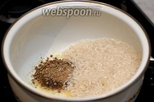Сливочное масло положить в кастрюлю, добавить специи и рис.
