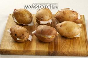 Одну половинку картофеля обмакиваем в соль, другую натираем выдавленным чесноком, и между половинками кладем кусочек сала.