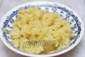 Слить воду с отваренного картофеля, размять его толкушкой, добавить 1/3 зажарки, сливочное масло, соль и перец по вкусу и хорошо перемешать. Дать начинке остыть.