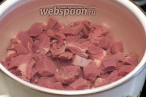 Выложить мясо в кастрюлю объемом 4 литра и залить холодной водой. Варить говядину 1,5 часа с момента закипания на медленном огне, снимая пену.