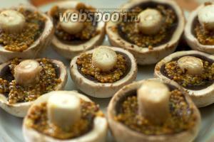 Смазать шляпки грибов горчицей с зёрнышками.