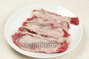 Мясо (500 г) помыть, порезать на тонкие куски, не более 1 см поперёк волокон, и обмакнуть в манную крупу (0,5 стакана). Очень важно правильно нарезать говядину, если она будет разрезана вдоль волокон, вы не сможете прожевать мясо, проще говоря, оно будет резиновое.