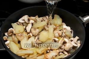Добавить грибы к картошке и влить стакан тёплой кипячёной воды. Тушить под крышкой 10-12 минут.  Если вы использовали сухие грибы, то добавляйте их к картошке вместе с бульоном, в котором их замачивали, и тоже тушить под крышкой.