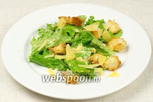 На каждую тарелку выложить листья салата, заправленные соусом, сверху немного крутонов и всё посыпать пармезаном. Классический салат Цезарь готов!
