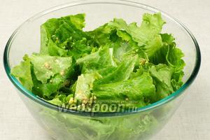 Добавить к листьям салата заправку и хорошо всё перемешать.
