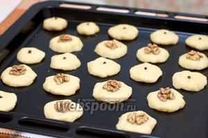 Выкладываем печенье на противень на расстоянии примерно 2 см друг от друга, из одной порции получается 20-22 штуки. В центр вставляем гвоздику или кладём половинку ореха.