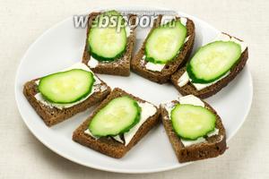 Ломтики хлеба разрезать на 2 части, тонко смазать сливочным маслом и сверху положить по кружочку свежего огурца.