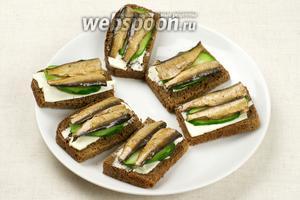 На огурец положить по 2 рыбки, предварительно удалив у них хвосты. Перед подачей присыпать мелко порезанным зелёным луком (0,5 пучка). Вот такие красивые бутерброды со шпротами у нас получились.