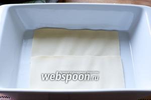 В огнеупорную форму, на дно выложить листы теста для лазаньи.  Перед использованием теста, ознакомьтесь с инструкцией по использованию на упаковке, так как существуют разные сорта теста и некоторые из них требуют предварительной подготовки.