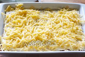 Верхний слой теста смазать соусом и хорошо посыпать сыром.