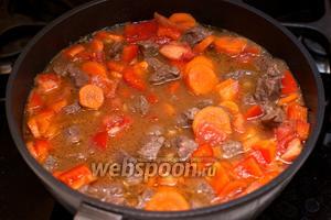 Добавить к мясу овощи — перец, морковь, помидоры и чеснок, добавить ещё 0,5 стакана воды, соль и перец, готовить 15-20 минут под крышкой, помешивая.