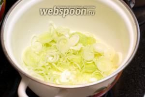 В кастрюле растопить сливочное масло и добавить лук-порей.