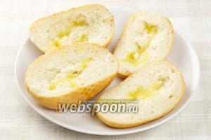 Булочки разрезать пополам, придавить мякоть, чтобы получилось углубление и сбрызнуть оливковым маслом.