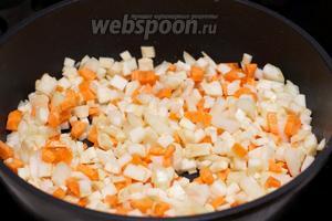 В большой сковороде или кастрюле с толстым дном разогреть 2-3 столовые ложки оливкового масла, а затем обжарить овощи: сельдерей, лук, морковь и чеснок — 10 минут, чтобы лук стал прозрачным.