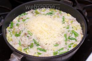 Когда рис будет готов, снять ризотто с огня, добавить сыр и хорошо всё перемешать.