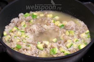 Затем начинаем добавлять горячий бульон по 1 поварешке. Постоянно помешиваем рис с овощами пока бульон не впитается, и только потом опять добавляем следующую поварешку бульона.