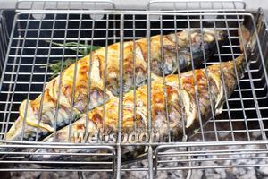 Решётку периодически поворачивать, чтобы рыба равномерно пропеклась и получилась золотистая корочка.