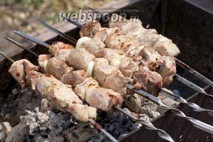 Шампура с мясом постоянно прокручивать над углями, чтобы шашлык равномерно разогревался и румянился.