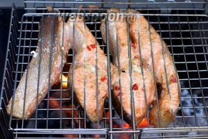 Решётку постоянно переворачивать, чтобы рыба равномерно пропеклась. Подавать с овощами.