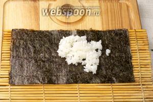 Сверху, руками смоченными в воде, выложить слой риса толщиной 3-5 мм.