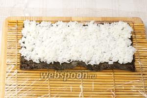 Макису предварительно завернуть в пищевую плёнку. Выложить на неё половину листа нори, а сверху рис ровным слоем толщиной 3-5 мм.