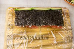 Затем перевернуть нори, так чтобы лосось оказался на макисе. И уложить с одного края нори полоски авокадо.