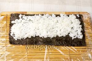 Завернуть макису в пищевую плёнку. Разрезать листы нори пополам.  Положить половину нори на макису, сверху выложить слой риса толщиной 1-1,5 см.