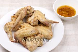 Готовые крылышки подавать горячими, поливая цитрусовым соусом.