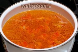 В процеженный бульон добавляем лук с помидорами и даем супу закипеть.